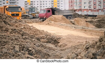 Dump trucks working on a construction site - Construction...