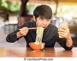 Man eating whilst looking and using smartphone - Man eating...