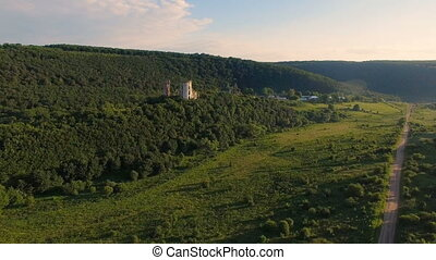 Aerial view of old castle, two towers and forest around
