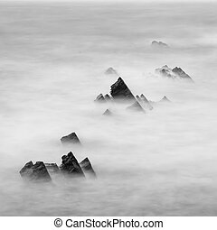 Beautiful long exposure landscape image of sea over rocks during sunset in black and white