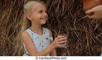 Cute blond girl drinks fresh cow's milk from a glass against haystack in summer on farm.