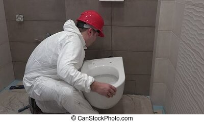 Skilled plumber man hanging heavy toilet bowl pan in new...