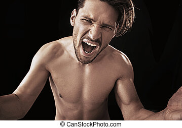 Aggressive screaming man posing on a black background