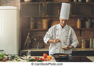 Mature man professional chef cooking meal indoors - Mature...