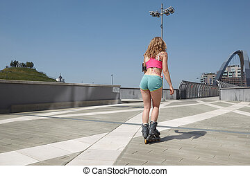Skating woman on rollerblades in urban environment