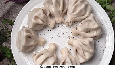 khinkali with pepper is spinning on a plate - khinkali is...