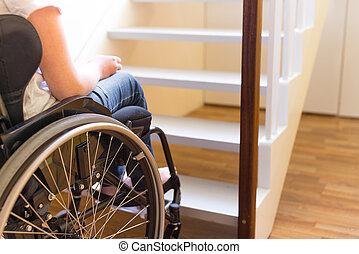 Person in a wheelchair in front of a stair - Young person in...