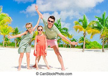 Father and little daughters having fun on white beach in...