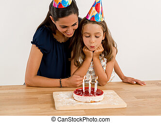Blowing out the candles - Shot of a mother and daughter in...