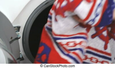 Hand puts towel inside steel washing machine drum - Person's...