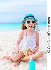 Happy smile girl with suncream bottle on the beach in sunny...