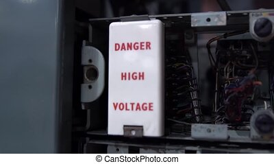 Danger high voltage sign. Old telephone dial station. 1960s