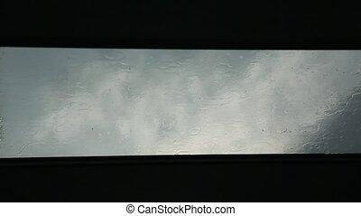Rain drops running down a window pane. Blue tint. - Rain...