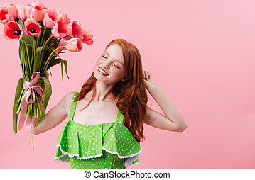 Image of Smiling ginger woman holding bouquet flowers -...