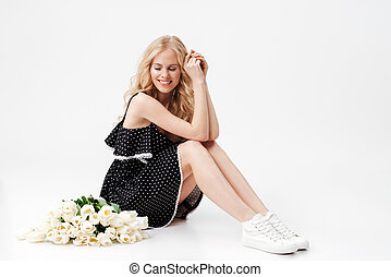 Beauty Blonde woman sitting on floor with bouquet of flowers...