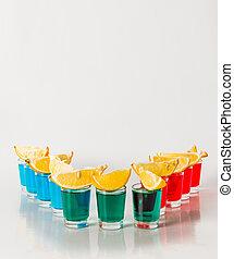 Eleven color shot drinks, red, blue and green kamikaze, quarters of lemon