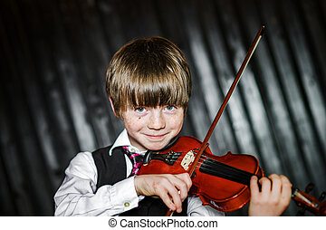 Attractive boy playing violin, studio shooting, music...