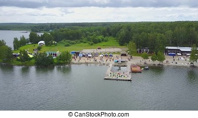 Aerial view of a coastal pier in the lake. Beautiful aerial view of the from above. Stunning beach landscape view with people walking down the pier. Aerial view on the beach and forest