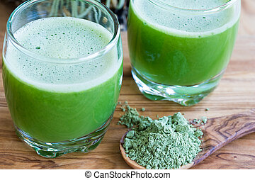 Barley grass powder on a spoon, with two barley grass shots...