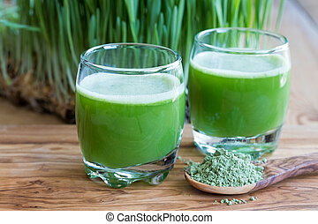 Two barley grass shots on a wooden background - Two green...