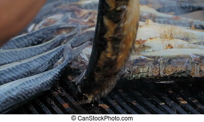 Mackerel hot smoked. Carcasses of fish in grill from which there is a light smoke