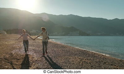 couple resting on shore of lake, husband take hands of wife, running