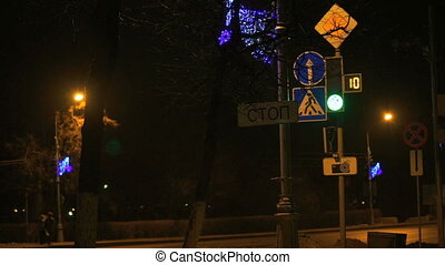 Intersection. Traffic light working at dark time. Cars stop...