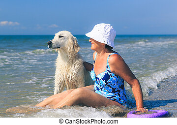 Elderly woman with her golder retriever on a sea
