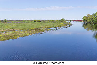 Valley river in reserve - Calm wide river flows across plain...