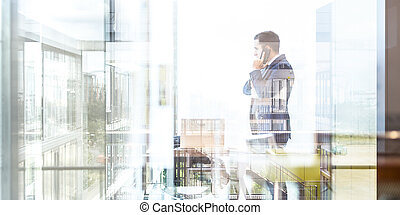 Businessman talking on a mobile phone while looking through...