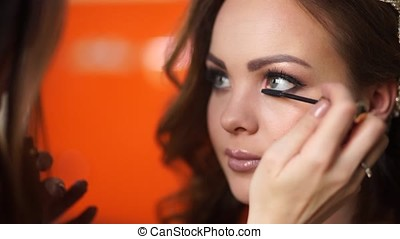 Make-up artist makes up the eyelashes of the bride to the girl.