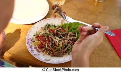 Someone eats meat salad with a fork and a knife. close-up....