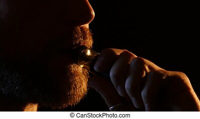 Guy exhales smoke into a dark room. Black background. Close...