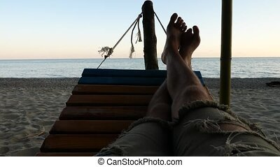 Feet swinging in a hammock, Relaxing on the beach at sunset. slow motion