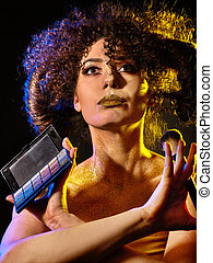 Woman with decorative cosmetics. Girl holds eye shadow and...