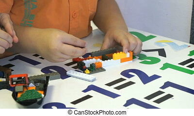 Child playing intellectual game with the designer