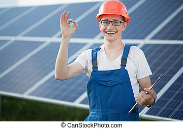 Worker on solar power station. Young man smailing, showing...