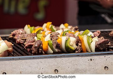 Chicken, beef and onion kabobs on a barbecue grill cooking...