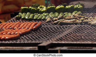 Sausage on a barbecue to cook at a fair ground. - Sausage on...