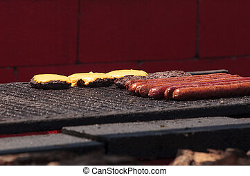 Sausage and hamburger on a barbecue to cook at a fair ground...