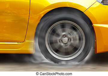 Gold car racing spinning wheel burns rubber on floor.