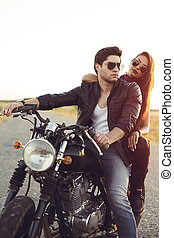 Sexy couple of bikers on the vintage custom motorcycle