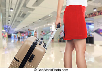 Business woman traveling and holding suitcase in the...