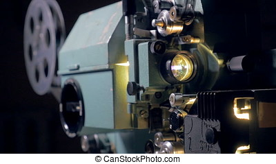 Old-fashioned movie projector in operation. - Old-fashioned...