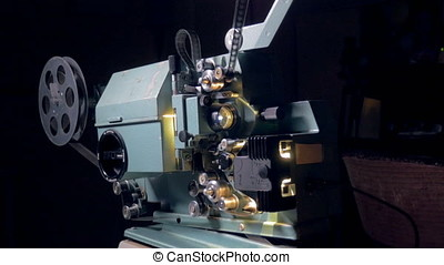 Opto-mechanical movie projector in operation. -...