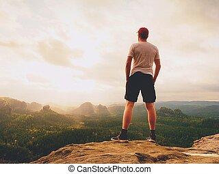 Tall man enjoy freedom on peak of mountain edge. Alone...