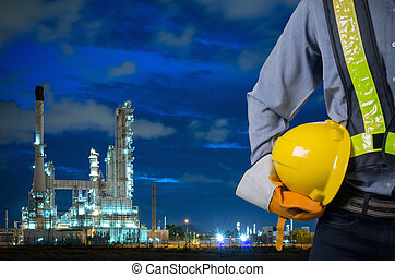 Engineer holding yellow helmet with oil refinery.