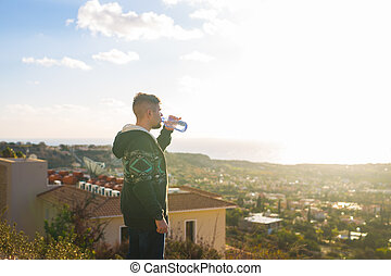 Young man standing on top of mountain with gorgeous view...