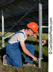 Technician installing foundation of solar panel with helical...