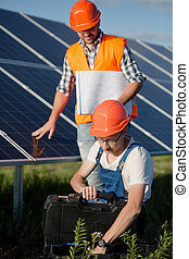 Workers at solar power station. Technicians checking out...